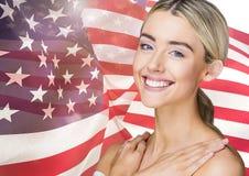 Lächelnde blonde Frau gegen amerikanische Flagge Stockfoto