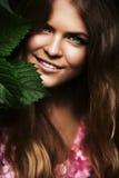Lächelnde blonde Frau hinter Blättern Stockfotografie