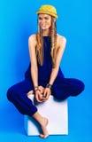 Lächelnde blonde Frau im blauen Gesamtsitzen auf Stuhl Lizenzfreie Stockbilder