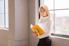 Lächelnde blonde Frau im modernen Büro Klassische Art Lizenzfreie Stockfotos