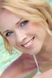 Lächelnde blonde Frau im Pool Stockfotos