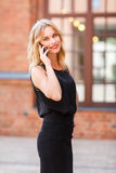 Lächelnde blonde Frau im schwarzen Geschäft kleidet die Unterhaltung auf Mobiltelefon Stockbilder