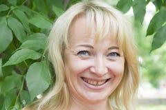Lächelnde blonde Frau im Sommer Stockbilder