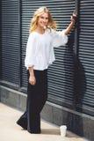 Lächelnde blonde Frau im vollen Wachstum nahe der schwarzen Wand Lizenzfreies Stockfoto