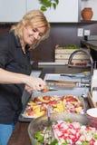 Lächelnde blonde Frau kocht gebratene Kartoffeln Lizenzfreies Stockfoto