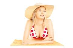 Lächelnde blonde Frau mit dem Hut, der auf einem Badetuch und einer Aufstellung liegt Stockfotos
