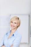 Lächelnde blonde Frau mit den gekreuzten Armen Lizenzfreie Stockfotos