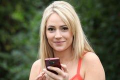 Lächelnde blonde Frau mit einem Handy Lizenzfreie Stockfotos