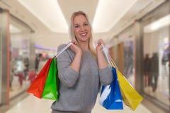 Lächelnde blonde Frau mit Einkaufstaschen Stockfoto