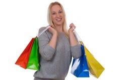 Lächelnde blonde Frau mit Einkaufstaschen Lizenzfreie Stockbilder