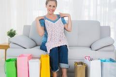Lächelnde blonde Frau mit Einkaufstaschen eine Spitze ausprobierend Stockfotos