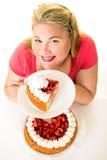 Lächelnde blonde Frau mit Erdbeercremekuchen Stockbild