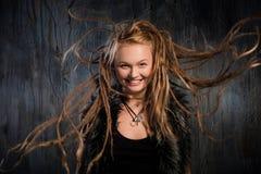 Lächelnde blonde Frau mit flatternden Dreadlocks Stockfotografie