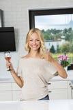 Lächelnde blonde Frau mit Glas Wein Stockbilder