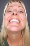 Lächelnde blonde Frau mit lustigem Gesicht Lizenzfreies Stockbild