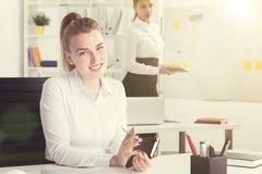 Lächelnde blonde Frau mit Notizbuch, Sonnenlicht Stockbild