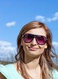 Lächelnde blonde Frau mit Sonnenbrillen draußen Stockbild