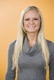 Lächelnde blonde Frau mit Strickjacke. Lizenzfreie Stockfotos
