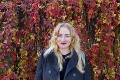 Lächelnde blonde Frau nahe bunten Blättern Stockfoto