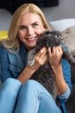 Lächelnde blonde Frau spielt mit ihrer Katze Stockbilder