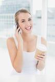 Lächelnde blonde Frau am Telefon, das Kaffee hält Lizenzfreie Stockfotografie