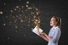 Lächelnde blonde Frau und Buch mit Buchstaben Stockfoto
