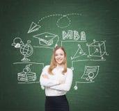 Lächelnde blonde Frau und MBA-Skizze, Tafel Stockfotografie