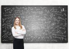 Lächelnde blonde Frau und Tafel mit Formeln Stockbilder