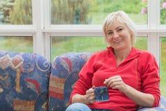Lächelnde blonde Frau von mittlerem Alter ist auf einem Sofa entspannend Stockfotos