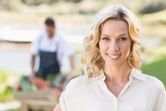 Lächelnde blonde Frau, welche die Kamera betrachtet Lizenzfreies Stockfoto