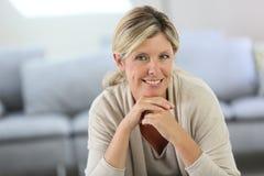 Lächelnde blonde Frau zu Hause Lizenzfreies Stockbild