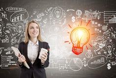 Lächelnde blonde Frauen- und Geschäftsikonen mit einer Glühlampeskizze Stockfotografie