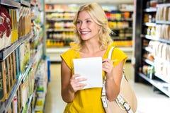 Lächelnde blonde Frauenprüfungsliste Lizenzfreie Stockfotos