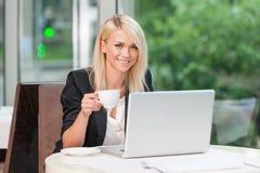 Lächelnde blonde Geschäftsdame, die Kamera betrachtet. Lizenzfreies Stockbild
