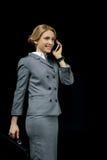 Lächelnde blonde Geschäftsfrau, die Aktenkoffer hält und auf Smartphone spricht Lizenzfreies Stockbild
