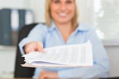 Lächelnde blonde Geschäftsfrau, die ein Papier führt Lizenzfreie Stockfotos