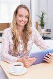 Lächelnde blonde Geschäftsfrau, die ihre digitale Tablette verwendet Stockbild
