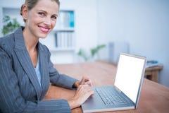 Lächelnde blonde Geschäftsfrau, die an Laptop arbeitet Lizenzfreies Stockfoto