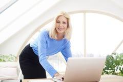 Lächelnde blonde Geschäftsfrau, die Laptop verwendet Lizenzfreies Stockbild
