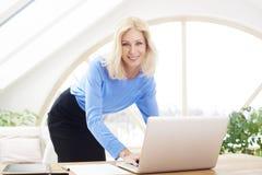 Lächelnde blonde Geschäftsfrau, die Laptop verwendet Stockfotografie