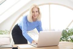 Lächelnde blonde Geschäftsfrau, die Laptop verwendet Stockfoto