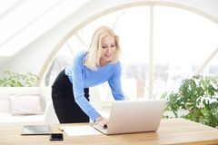 Lächelnde blonde Geschäftsfrau, die Laptop verwendet Lizenzfreies Stockfoto