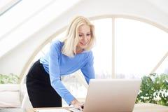 Lächelnde blonde Geschäftsfrau, die Laptop verwendet Stockbild