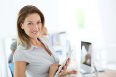Lächelnde blonde Geschäftsfrau, die Tablette im Büro verwendet Lizenzfreies Stockbild