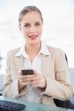 Lächelnde blonde Geschäftsfrauversenden von sms-nachrichten Stockfoto