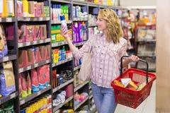 Lächelnde blonde hübsche Frau, die Produkt betrachtet Stockfotografie