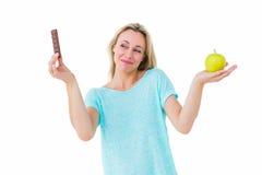 Lächelnde blonde haltene Schokolade und Apfel Lizenzfreie Stockbilder