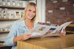 Lächelnde blonde haltene Zeitung Lizenzfreies Stockfoto