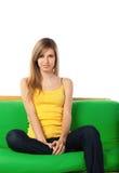 Lächelnde blonde junge Frau auf Sofa Stockfotos