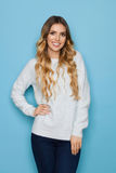Lächelnde blonde junge Frau in der blauen Pastellstrickjacke Stockfotos